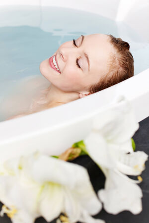 soaking: Beautiful young woman with her eyes closed smiling in pleasure in a curved spa bath with white flowers in the foreground Stock Photo