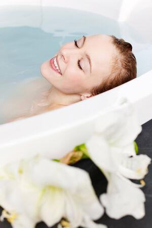 éxtasis: Joven y bella mujer con los ojos cerrados sonriendo de placer en una bañera de hidromasaje curvada con flores blancas en el primer plano