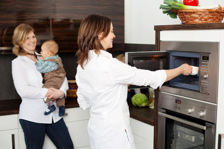babyboy: Mid adult woman keeping cup in microwave with friend carrying babyboy in background at kitchen Stock Photo
