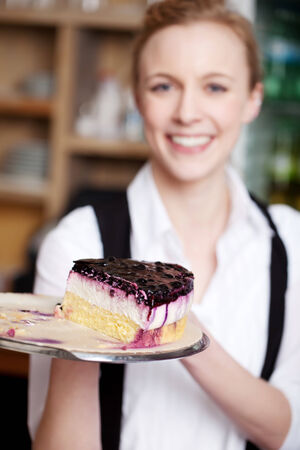 unhealthful: Portrait of happy waitress with cake tray in cafe