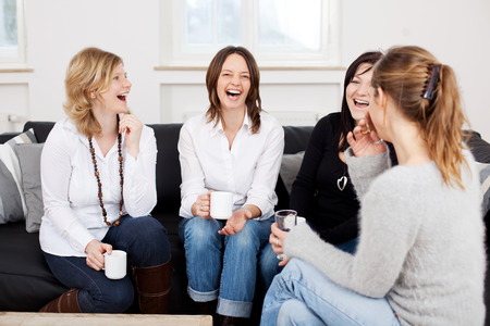 mate drink: Female friends holding coffee cups while laughing on sofa at home