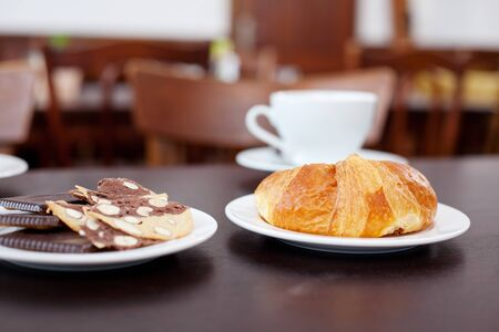 unhealthful: Closeup of croissant and chocolates with crackers on table at restaurant