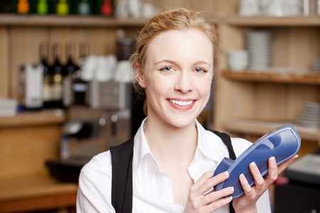 swipe: Portrait of happy waitress holding swipe machine in restaurant