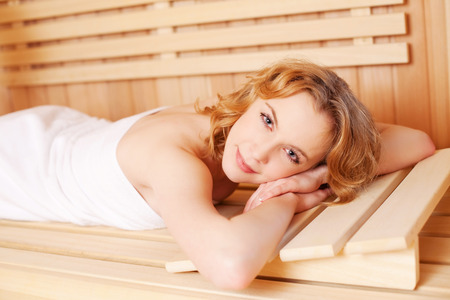 perspire: Woman relaxing in a wooden sauna lying on her stomach on the bench with a drowsy expression and towel wrapped around her body
