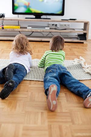 viendo television: Vista posterior de cuerpo entero de hermano y hermana que mienten en la alfombra mientras se ve la televisi�n en casa