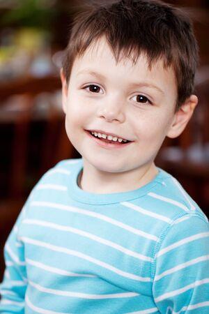 waistup: Portrait of cute little boy smiling in restaurant