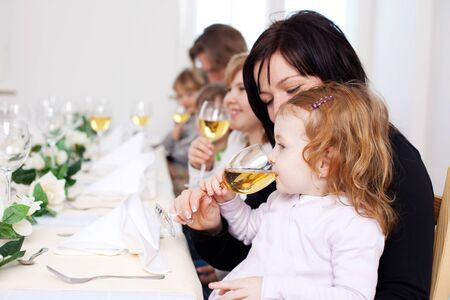 Cute little girl seated on her mothers lap at a party getting her first taste of white wine from her mothers glass photo