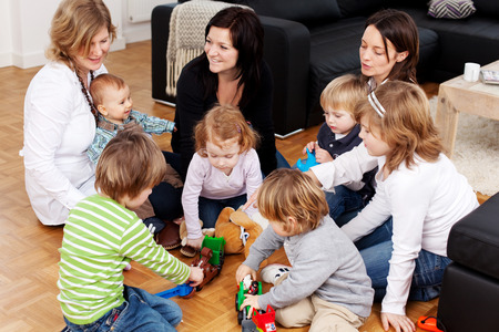 Group of mothers and young children sitting together on a wooden floor at a party with the kids playing with colourful plastic toys