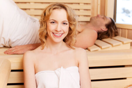 perspire: Beautiful young woman with a lovely warm smile in a traditional wooden sauna with her boyfriend or husband Stock Photo
