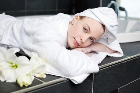 lying in bathtub: Portrait of beautiful young woman in bathrobe lying at spa
