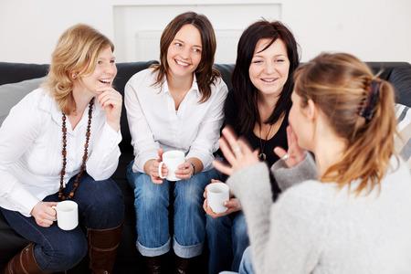 집에서 의사 소통하는 동안 커피 컵을 들고 행복 한 여자 친구 스톡 콘텐츠