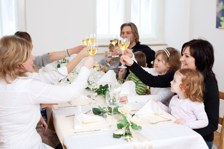 socializing: Group of happy family and friends toasting wineglasses at table in restaurant