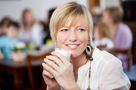 fringes: Closeup of young woman holding coffee cup while looking away in restaurant