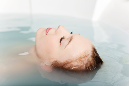 closed: Woman soaking in a bath tub with just her face above the water with her eyes closed and a beautiful serene expression