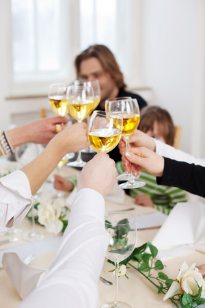 children celebration: Closeup of hands toasting wineglasses over table in restaurant