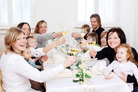 Retrato de familia feliz y amigos tostado copas de vino en la mesa de restaurante