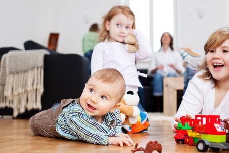 Adorable baby boy crawling on a wooden floor reaching for a toy and looking up with a happy intelligent expression as someone attracts his attention photo