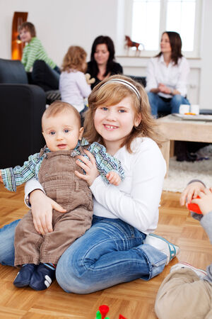 preadolescent: Portrait of happy preadolescent girl with baby sitting on floor at home Stock Photo