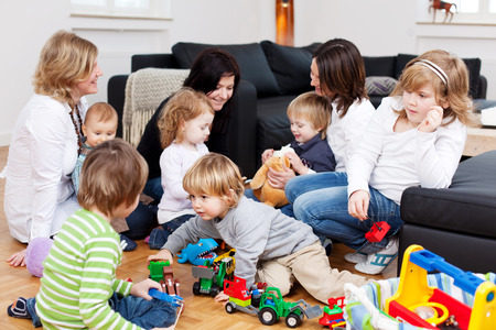 socializing: Little children playing while sitting with mothers on hardwood floor at home