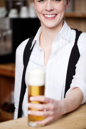 Smiling woman with a pint of beer in a tall glass in her hand with focus to her smiling mouth photo