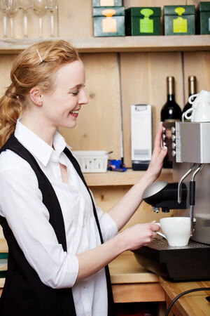 dispensing: Smiling waitress dispensing filter coffee from a coffee machine in a restaurant or coffee house
