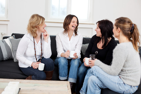 Happy female friends with coffee cups sitting on sofa at home Banco de Imagens