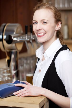 Smiling waitress in a bar standing behind the counter with her hands resting on a portable credit card machine for payment for services photo