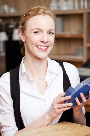 Vivacious pretty young waitress with a portable card machine in her hands for payments by bank cards photo