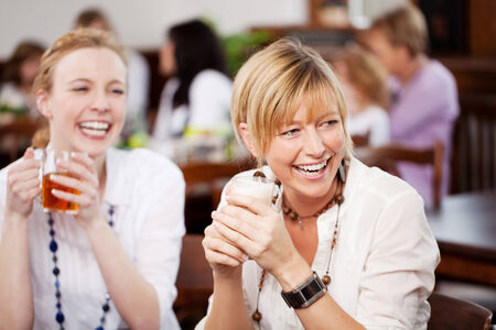 Two attractive vivacious female friends laughing over refreshments in a restaurant as they watch something off frame photo