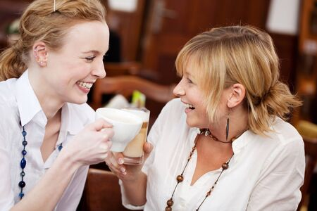 Closeup of happy young women toasting coffees in restaurant photo