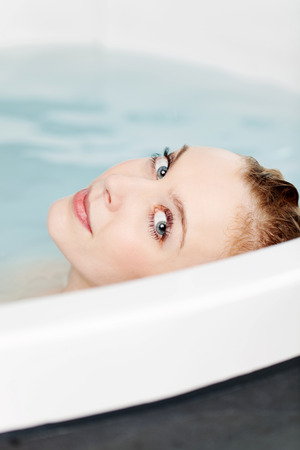 Beautiful woman relaxing in a bath looking back over the top of the rim at the camera while soaking in the water photo