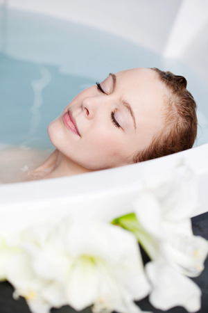 soaking: Absolute bliss as , a beautiful woman relaxes in a spa tub in the warm water with her eyes closed and a serene expression Stock Photo