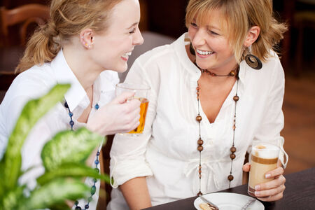 Two women laughing in a restaurant as they sit together at a table enjoying a glass of tea and coffee together photo