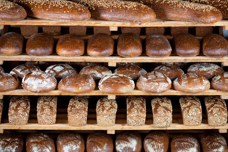 Variety of delicious breads displayed on shelves in bakery Stock Photo