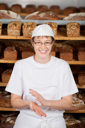 food sales: smiling female worker in bakery standing against shelves Stock Photo