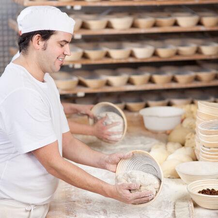haciendo pan: Cocinero de sexo masculino que pone la masa en un recipiente para hornear con un compañero de trabajo en segundo plano en el mostrador de la cocina Foto de archivo