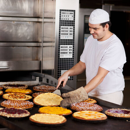 fresh bakery: Mid adult male worker baking various pie in bakery kitchen