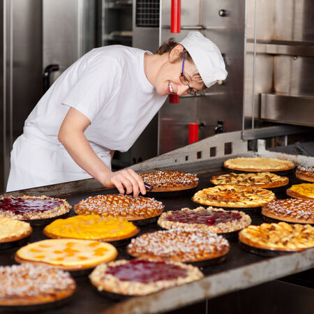Mid adult female worker checking pies temperature on oven tray Stock Photo