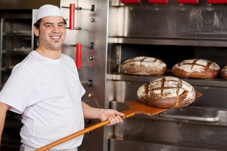 baking bread: Portrait of happy mid adult male worker baking bread in kitchen at bakery Stock Photo