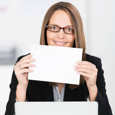 black rimmed: Smiling businesswoman wearing black rimmed glasses with a blank white sign or card in her hands sitting at her laptop computer