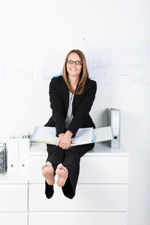 Happy businesswoman working from home sitting on top of a white filing cabinet swinging her bare feet in the air with a playful smile photo