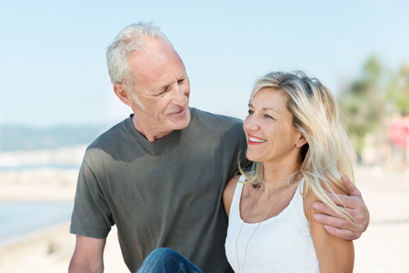 Happy mature couple on a tropical beach standing arm in arm in an intimate embrace smiling at each other photo
