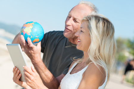 travelers: Happy middle-aged couple deciding on their next vacation standing on a beach consulting a globe and tablet computer as they check out global destinations Stock Photo