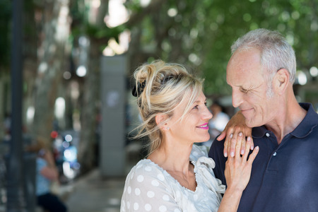 senior citizen: Loving attractive middle-aged couple looking tenderly at each other as they pause in the shade of leafy green trees Stock Photo