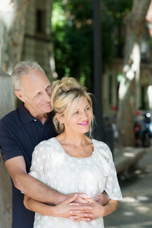 Mature couple sharing a tender moment as they stand in an intimate hug looking off to the right of the frame in a tree lined street photo