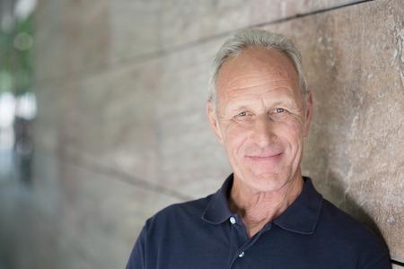 Lächelnde attraktive grauhaarige Mann, der neben einem zurückweichenden Außenwand, der die Kamera mit Copyspace