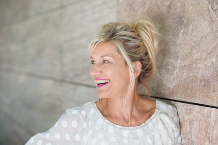 Vivacious beautiful blond woman posing leaning against a receding wall as she looks to the left with a laughing smile