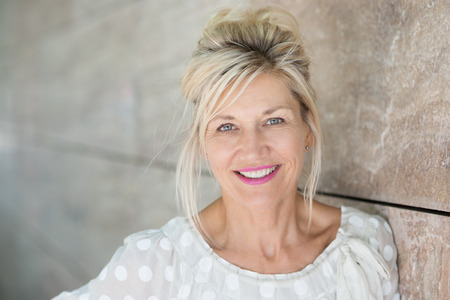 아름다운 미소 직접 카메라를 찾고 필사적으로 벽에 서 매력적인 중간 금발 여자