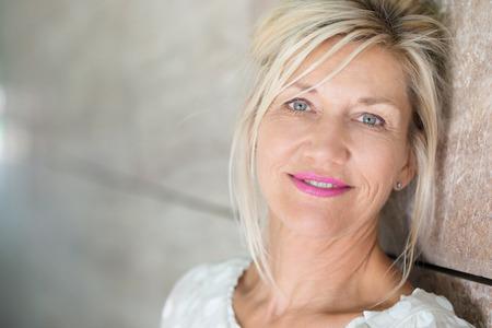 madre soltera: Mujer de mediana edad atractiva con el pelo rubio atado flojamente espalda mirando a la cámara con una sonrisa tranquila suave mientras ella se inclina contra una pared del retroceso con copyspace