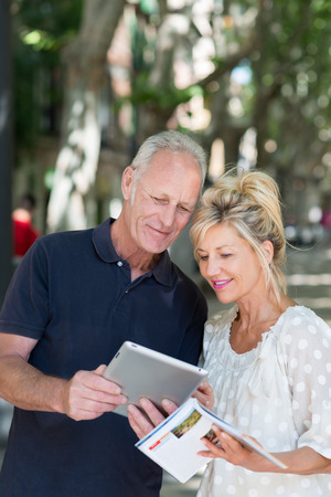 tour guide: Pareja comprobar la informaci�n sobre un equipo Tablet PC, ya que hacen referencia a un folleto de viaje durante las vacaciones de verano en una arbolada calle urbana Foto de archivo